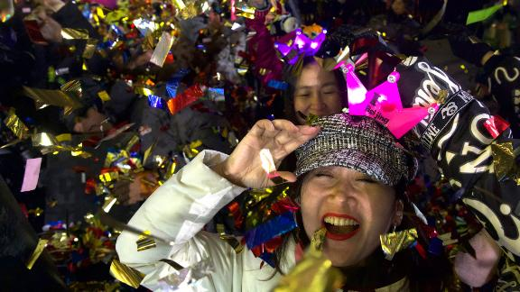 People celebrate the new year near the 2022 Beijing Winter Olympic headquarters.