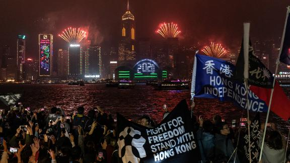 Pro-democracy supporters wave flags and shout slogans during a countdown party in the Tsim Sha Tsui district in Hong Kong.