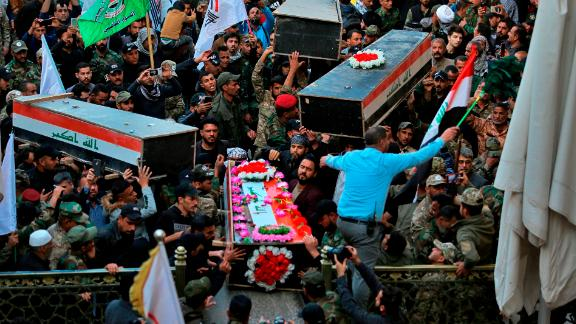 Mourners carry the coffins of Iranian-backed paramilitary fighters in Najaf, Iraq, on December 31. The fighters were killed in US airstrikes on Sunday that sparked Tuesday