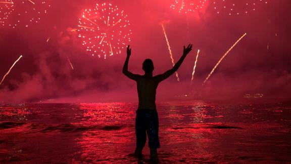 A man watches fireworks from Copacabana Beach in Rio de Janeiro, Brazil.