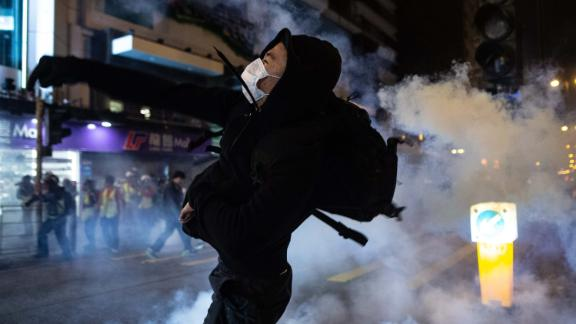 A protester reacts after police fire tear gas to disperse bystanders in the Jordan district of Hong Kong, early on December 25.