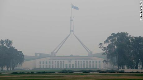 The Australian flag flies above Parliament House as smoke shrouds the Australian capital of Canberra, Australia, Wednesday, Jan. 1, 2020.