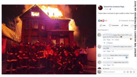"Detroit firefighters pose in front of a burning building in a photo that was later taken down by the Detroit Fire Incidents Page on Facebook. Although it isn't clear when it was taken, the initial caption was ""Crews take a moment to get a selfie on New Years!"""