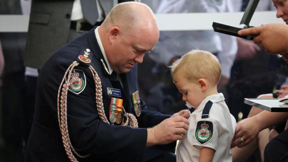Royal Fire Service Commissioner Shane Fitzsimmons presents a posthumous Commendation for Bravery and Service on January 2 to the son of RFS volunteer Geoffrey Keaton, who was killed battling bushfires, at Keaton