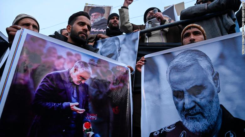 Protesters shout slogans against the United States and Israel as they hold posters with the image of Qasem Soleimani, who was killed in a US airstrike in Iraq, and Iranian President Hassan Rouhani during a demonstration in the Kashmiri town of Magam on January 3.