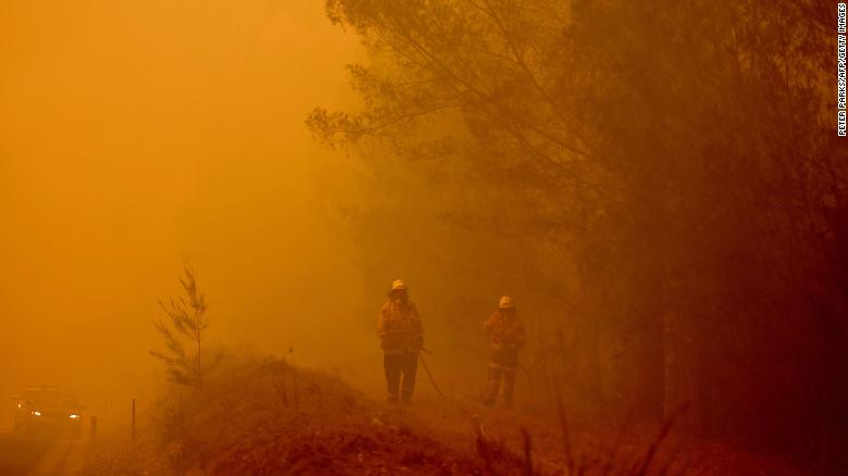 Firefighters tackle a bushfire in thick smoke in the town of Moruya, south of Batemans Bay, in the state of New South Wales on January 4.