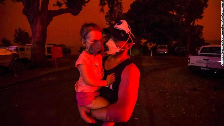 A father holds his daughter as the skies above turn red during the day on January 4 in Mallacoota, Australia. Many parents with young children were stuck in Mallacoota after flights were grounded because of smoke and only school-aged children and older were allowed to evacuate by boat.