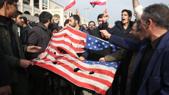 """TOPSHOT - Iranians tear up a US flag during a demonstration in Tehran on January 3, 2020 following the killing of Iranian Revolutionary Guards Major General Qasem Soleimani in a US strike on his convoy at Baghdad international airport. - Iran warned of """"severe revenge"""" and said arch-enemy the United States bore responsiblity for the consequences after killing one of its top commanders, Qasem Soleimani, in a strike  outside Baghdad airport. (Photo by ATTA KENARE / AFP) (Photo by ATTA KENARE/AFP via Getty Images)"""
