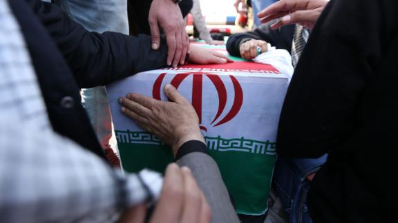 Mourners touch a casket draped in Iranian flags during Qasem Soleimani