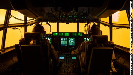 MERIMBULA, AUSTRALIA - JANUARY 05: In this handout provided by the Australian Department of Defence, the flight deck is lit by the red glow of the fires as the aircrew of a C-130J Hercules attempt to land at Merimbula airfield to drop off Fire and Rescue crews from the Mid-North Coast region of NSW, to assist fighting the bushfires on January 5, 2020 in Merimbula, Australia. One person has died overnight in Batlow and four firefighters were injured. A state of emergency is in place across NSW as firefighters battle 150 fires, 64 of which are uncontained. Prime Minister Scott Morrison on Saturday announced that army reservists were being called up to help with firefighting efforts across Australia, along with extra ships and helicopters. 14 people have now died in the fires in NSW, Victoria and South Australia since New Year's Eve. (Photo by Corporal Nicole Dorrett/Australian Department of Defence via Getty Images)