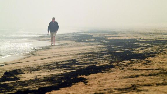 A man walks past ash from bushfires washed up on a beach in Merimbula on January 5.