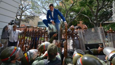 National Assembly President Juan Guaido, Venezuela's opposition leader, tries to climb the fence to enter the compound of the Assembly, after he and other opposition lawmakers were blocked by police from entering a session on Jan. 5, 2020.