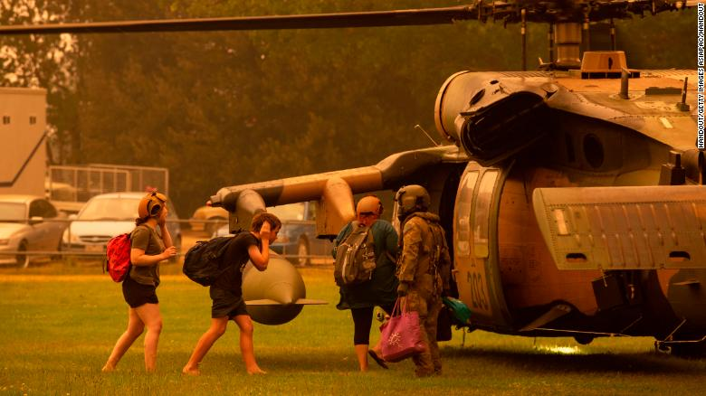 An Australian army soldier helps people evacuate onto a Black Hawk helicopter in Omeo, Victoria on January 5, 2020.
