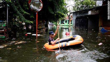 A man navigates an inflatable boat at a flooded neighborhood in Jakarta on Saturday.