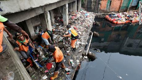 Workers collect trash during a clean up after flooding in Jakarta on Sunday.