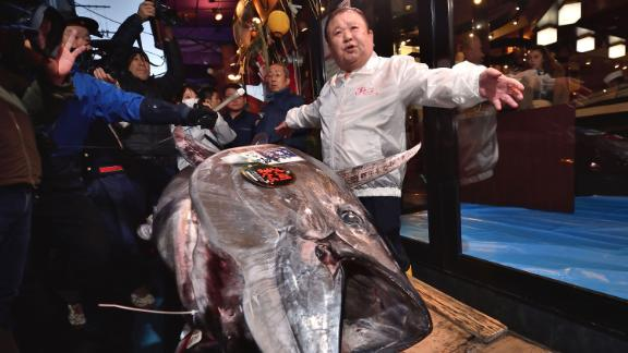 Kiyoshi Kimura (R), President of Kiyomura Corp., the Tokyo-based operator of sushi restaurant chain Sushizanmai, displays a 276-kilogram bluefin tuna that fetched 193.2 million yen (1.8 million USD) at his main restaurant in Tokyo on January 5, 2020 after the New Year's auction at Toyosu fish market.