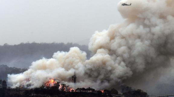 A military helicopter flies above a burning woodchip mill in Eden, New South Wales, on January 6.