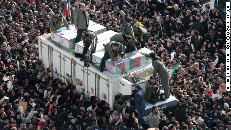 Iranian revolutionary guards surround the coffins of Soleimani and other victims during the procession.