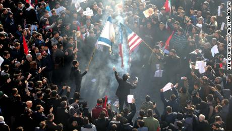 Iranians set a US and an Israeli flag on fire during Soleimani's funeral procession.