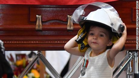 Charlotte O'Dwyer, the young daughter of Rural Fire Service volunteer Andrew O'Dwyer, stands in front of her father's casket wearing his helmet.