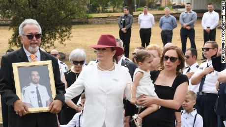 O'Dwyer's father, Errol, wife Melissa (in black) and young daughter Charlotte carried a portrait of the fallen firefighter at his funeral.