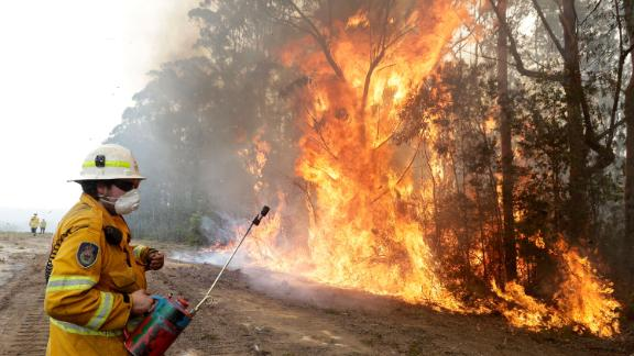 A firefighter backs away from flames after lighting a controlled burn near Tomerong on January 8.