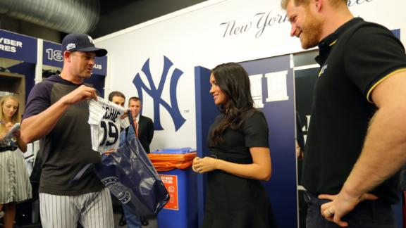 New York Yankees manager Aaron Boone presents the couple with a jersey for Archie before a Major League Baseball game in London in June 2019.