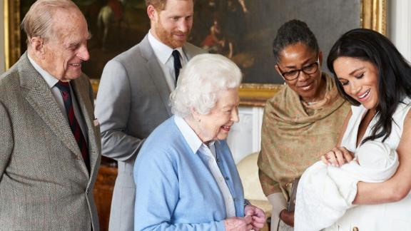 Queen Elizabeth II looks at her new great-grandchild, Archie, in May 2019. Prince Philip is on the far left. Meghan