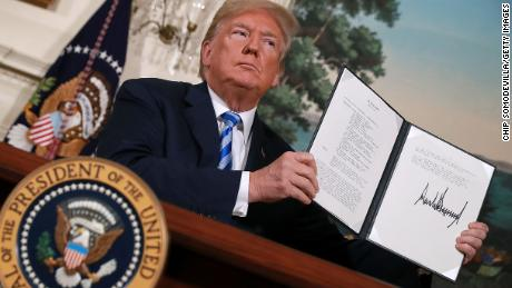 US President Donald Trump holds up a memorandum reinstating sanctions on Iran after he announced the US would withdraw from the Iran nuclear deal, at the White House on May 8, 2018.