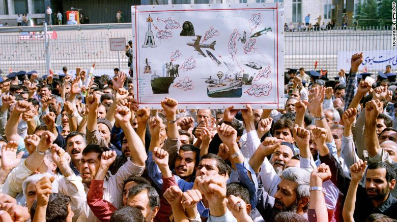 """Thousands of Iranians chanting """"Death to America,"""" participate in a mass funeral for 76 people killed when the USS Vincennes shot down Iran Air Flight 655, in Tehran, Iran, July 7, 1988. They hold aloft a drawing depicting the incident."""