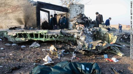 People stand near the wreckage after a Ukrainian plane carrying 176 passengers crashed near Imam Khomeini airport.
