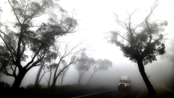 A vehicle makes its way through thick fog mixed with bushfire smoke in the Ruined Castle area of the Blue Mountains on January 11.