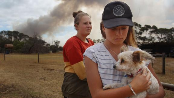 Bonnie Morris and sister Raemi Morris look on as their family and firefighters battle bushfires at the edge of their family farm in Karatta on Saturday, January 11.