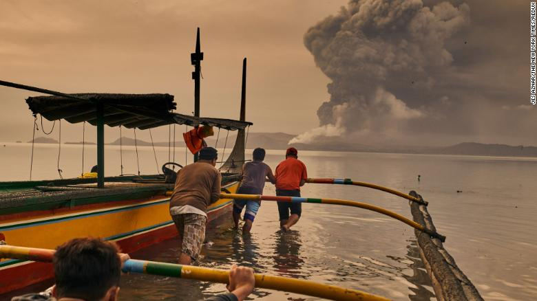 Residents prepare their boats to evacuate while the Taal Volcano erupts in Talisay, Philippines, on Monday, January 13. Tens of thousands were evacuated and tremors were felt in nearby villages amid an eruption of the country's second-most-active volcano near Manila.