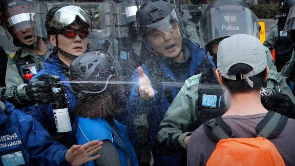 "A riot policeman sprays pepper spray at a man as they disperse a crowd during a demonstration against ""parallel traders"" who buy goods in Hong Kong to resell in mainland China on Sunday, January 5."