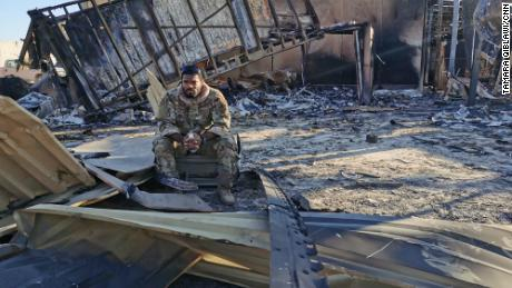 Sergeant Ferguson sits between charred metal at the site of the destroyed housing unit for drone pilots and operators.