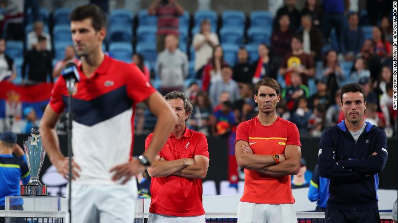 Rafa Nadal looks on as Novak Djokovic gives his victory speech following the ATP Cup final.