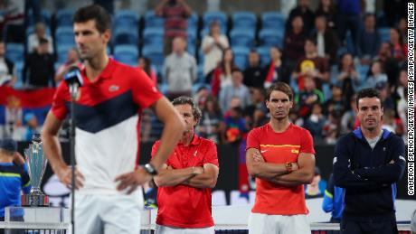 Rafa Nadal watches Novak Djokovic deliver his victory speech after the ATP Cup final.