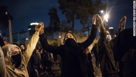 Iranians hold hands during a demonstration in front of Tehran's Amir Kabir University on January 11, 2020. - Demonstrations broke out for a second night in a row after Iran admitted to having shot down a Ukrainian passenger jet by mistake on January 8, killing all 176 people on board. (Photo by STR / AFP) (Photo by STR/AFP via Getty Images)