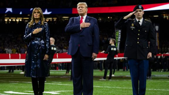 US President Donald Trump and first lady Melania Trump stand on the field for the National Anthem.