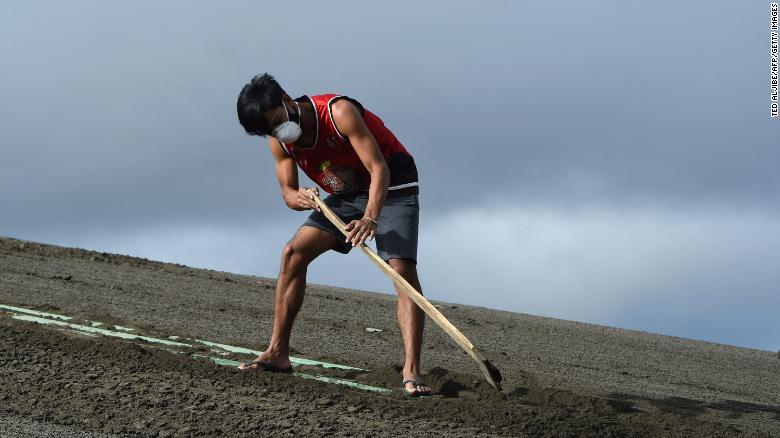 A resident cleans the roof of their house filled with ash spewed by Taal volcano in Tagaytay city.