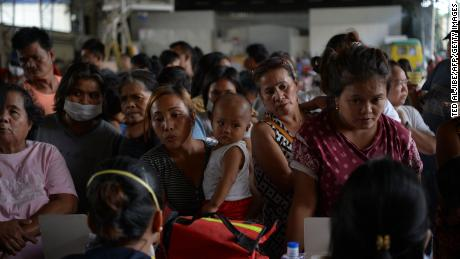 Evacuees from towns affected by the eruption of Taal volcano queue up to have their children checked by medical personnel at an evacuation center in Tanauan town.
