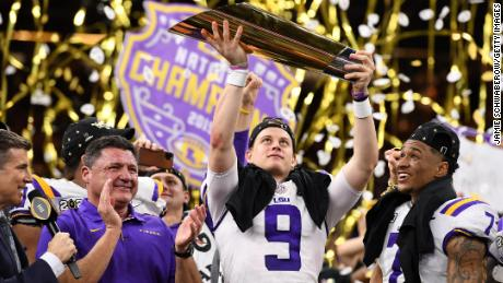 NEW ORLEANS, LA - JANUARY 13: Joe Burrow #9, head coach Ed Oregon and Grant Delpit #7 of the LSU Tigers receive the trophy after defeating the Clemson Tigers during the College Football Playoff National Championship held at the Mercedes-Benz Superdome on January 13, 2020 in New Orleans, Louisiana. LSU defeated Clemson 42-25 for the national title. (Photo by Jamie Schwaberow/Getty Images)