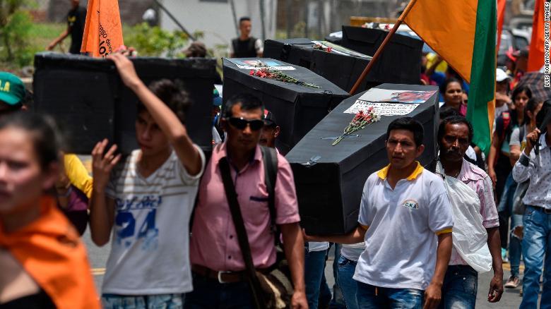 Жители несут самодельные гробы в знак солидарности с жертвами насилия в Кали, Колумбия, в апреле 2018 года.