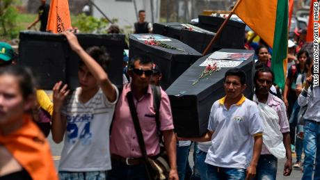 Residents carry makeshift coffins in solidarity with victims of violence in Cali, Colombia, in April 2018.