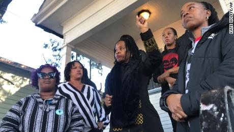 Sharena Thomas, left, Carroll Fife, center, Dominique Walker, second from right, and Tolani KIng, right, stand outside the vacant home they took over on Magnolia Street in West Oakland, California.