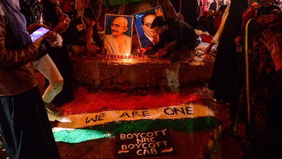 Protesters light candles near posters of Mahatma Gandhi and politician and social reformer Bhimrao Ramji Ambedkar during a demonstration against India