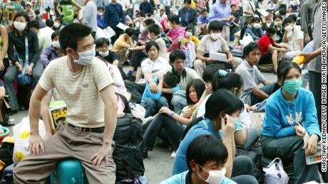 Migrant workers wait outside the Guangzhou train station before returning home because of the worry over SARS during the deadly epidemic in 2003.