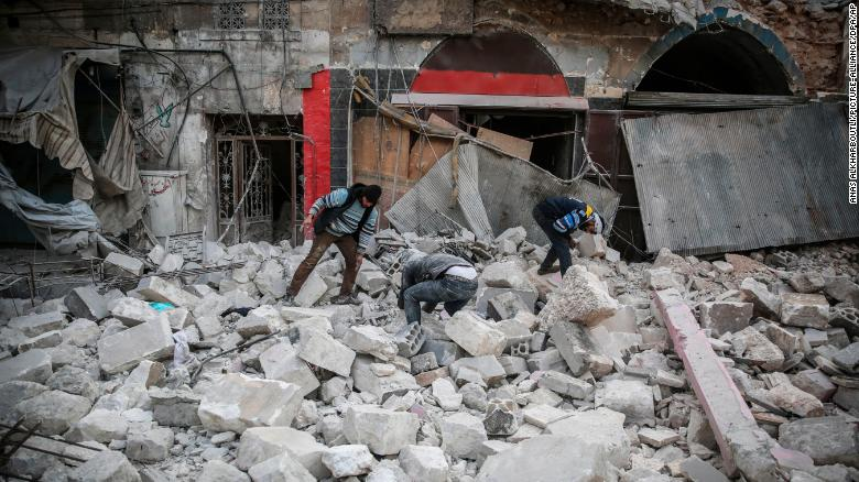 People search for victims or survivors under the rubble at the popular market in the city of Ariha on Jan. 15, airstrikes on the rebel-held Idlib province.