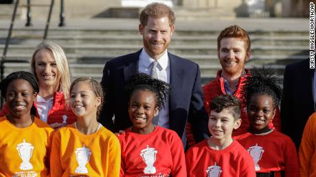 Prince Harry poses with schoolchildren and Rugby League World Cup 2021 ambassadors James Simpson, right, and Jody Cunningham in the gardens at Buckingham Palace.
